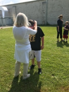 Mrs. Zelenak awarding 6th grader with their medal