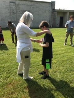 Mrs. Zelenak giving 6th grader his medal