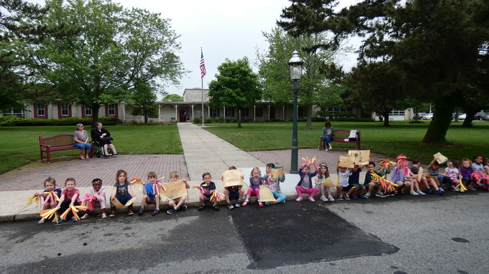 PreK students cheer on the bikers