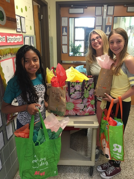 teacher and students holding cheer bags
