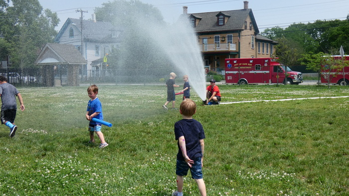 students running through water from fire hose