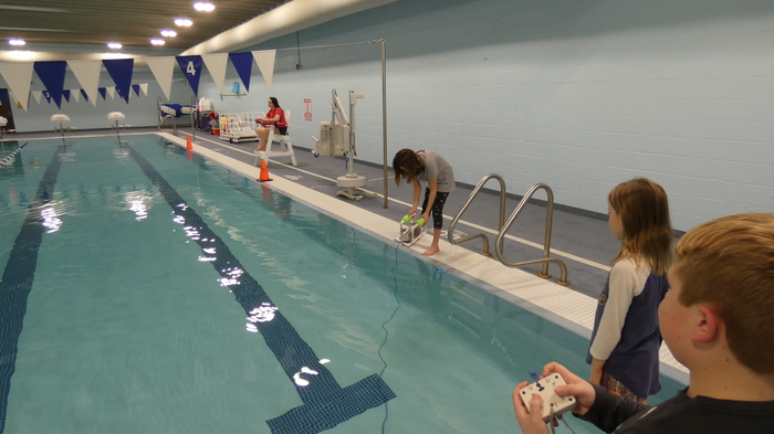 Student places SeaPerch in water
